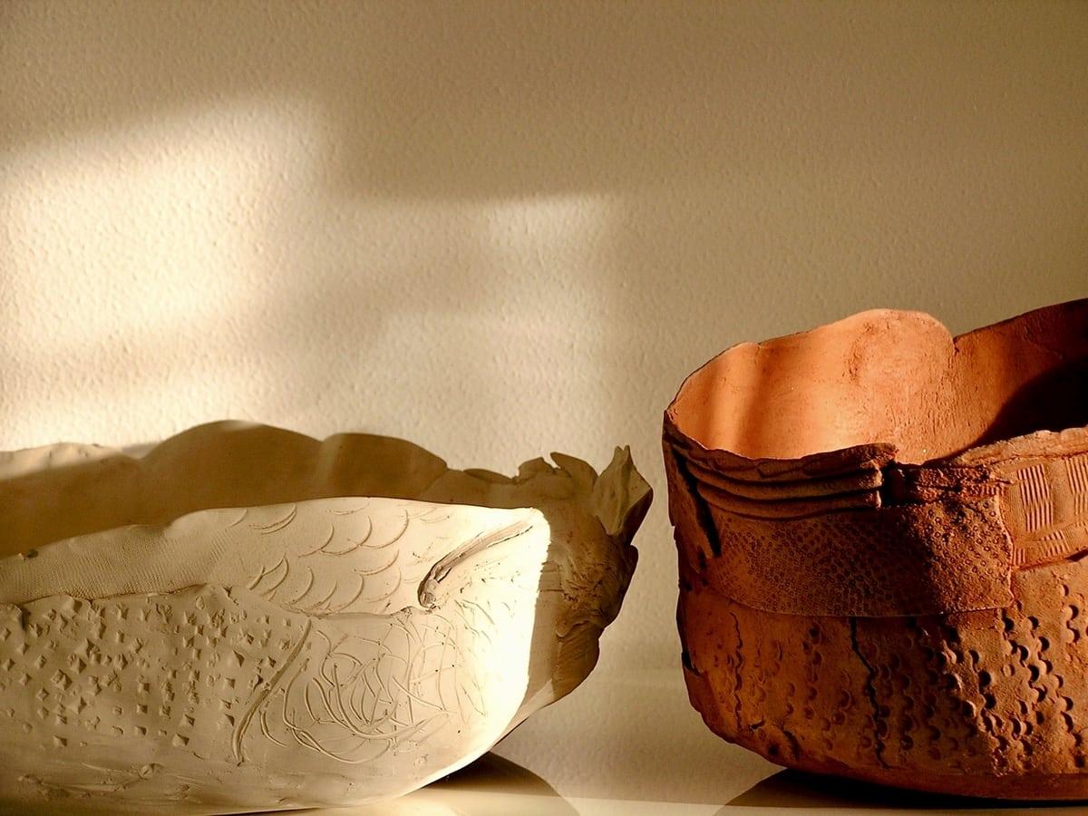 Dettagli di due ciotole in ceramica, una dal colore bianco e l'altra dal colore rosso mattone