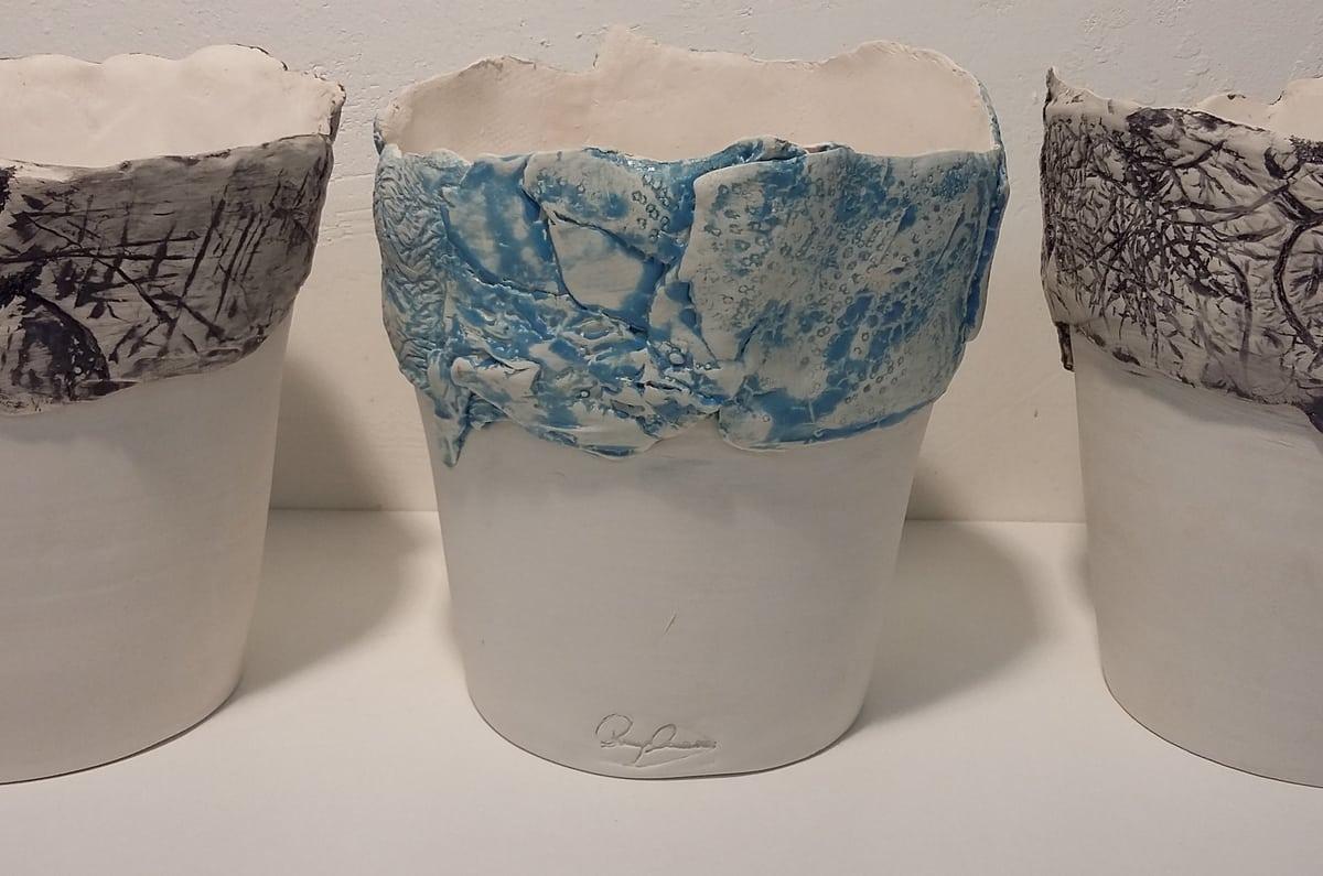 Tre vasi in ceramica bianca con dettagli in azzurro e nero con firma