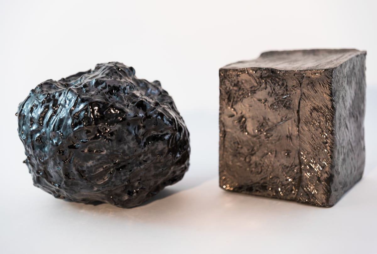 Coppia di oggetti in ceramica scura dalle forme geometriche
