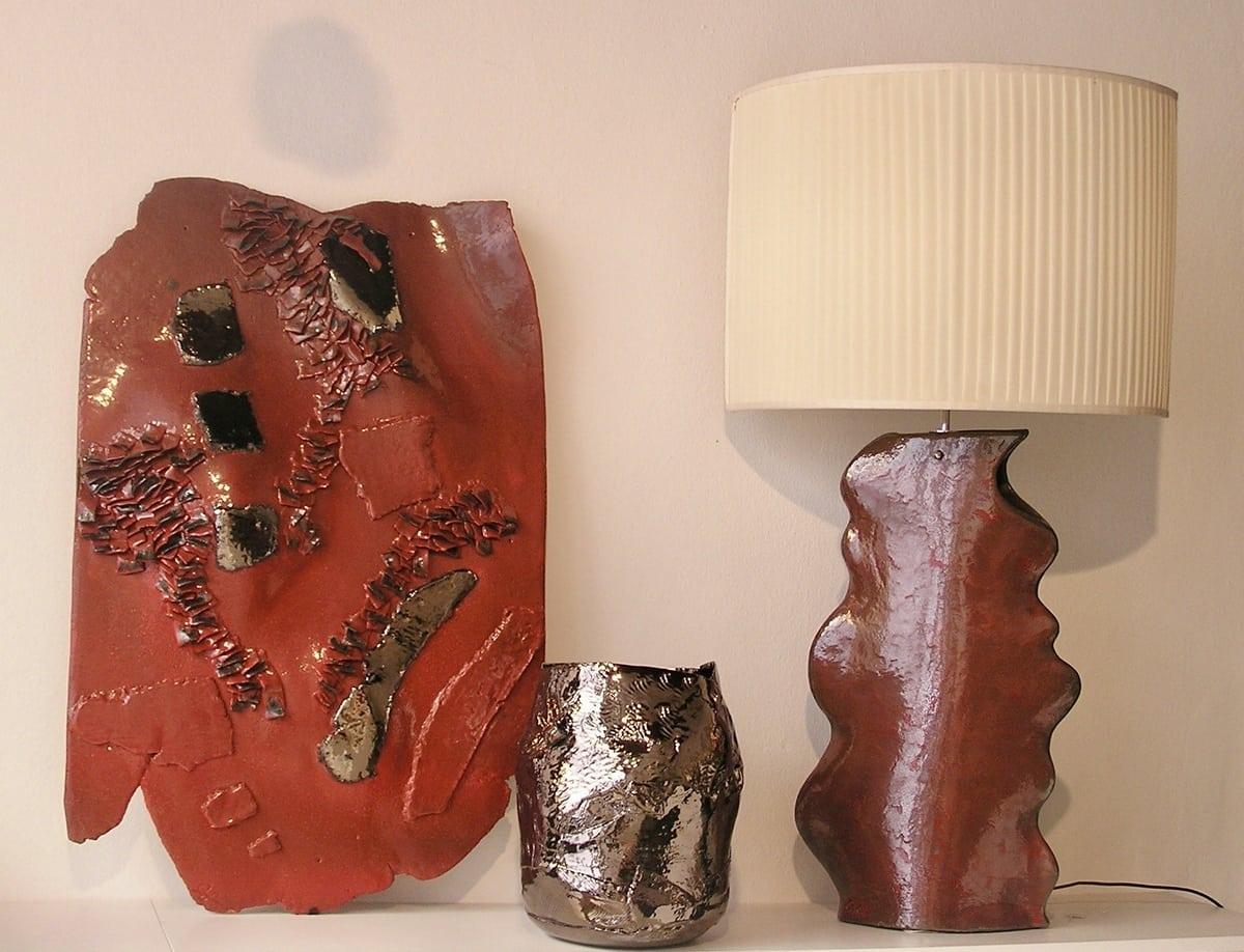 Oggetto da parete rosso e oro, vaso in ceramica lucida e lampada con base in ceramica dal colore rosso intenso