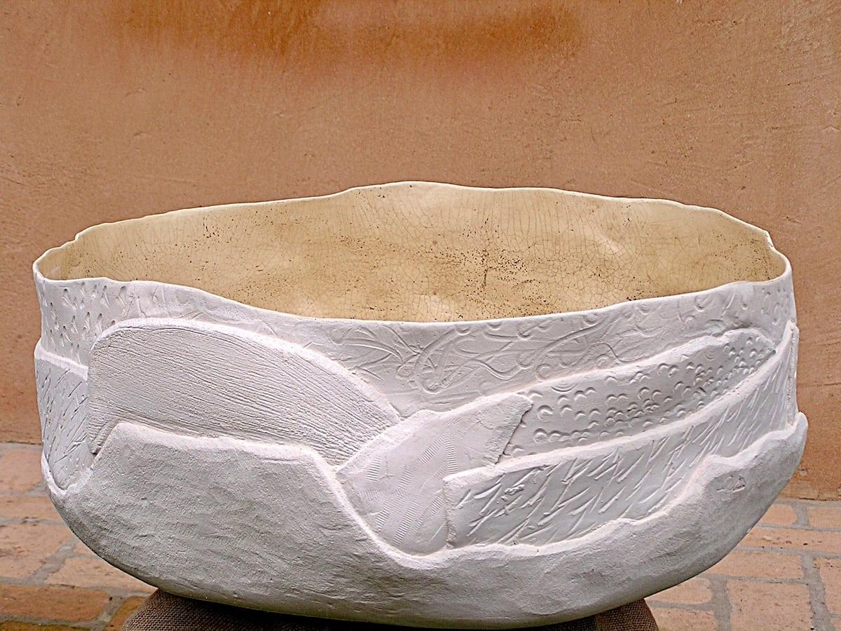 Esposizione di una grande ciotola in ceramica bianca con l'interno in sabbia