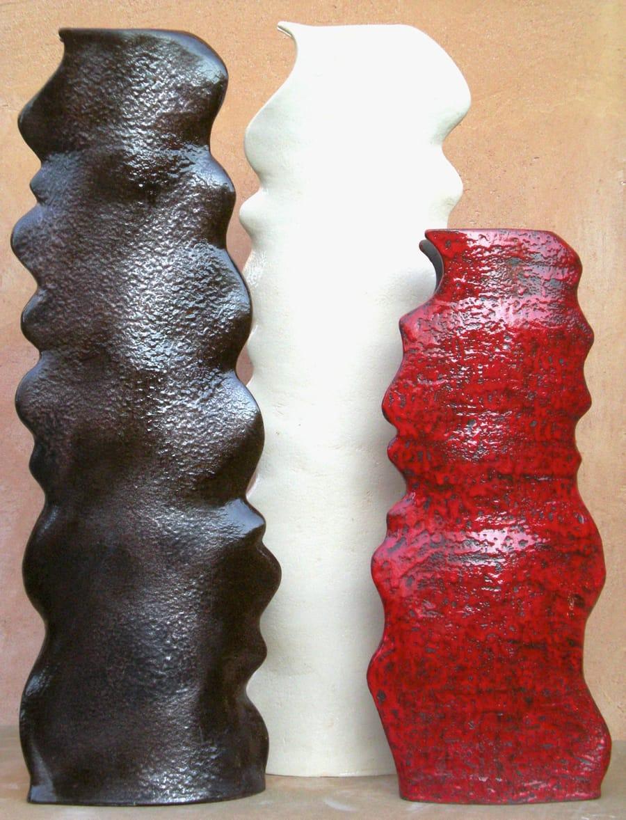 Esposizione di tre basi per lampade dal colore rosso, nero e bianco