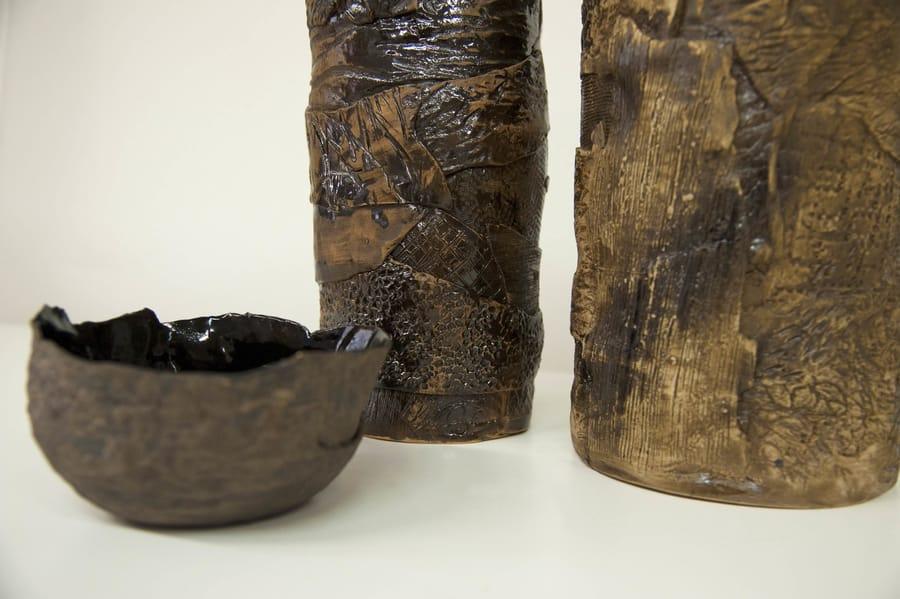 Esposizione di una ciotola e due vasi in ceramica scura