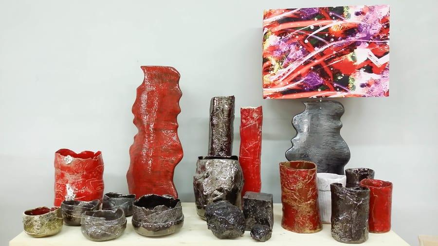Esposizione di oggetti in ceramica tra cui una lampada e diversi vasi e ciotole
