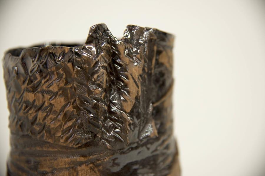 Dettaglio del vaso in ceramica scura dalla forma asimmetrica