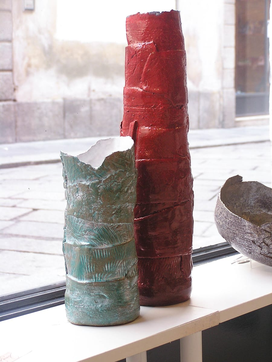 Esposizione di vasi in ceramica di diversi colori e dimensioni